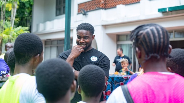 HERO: Micah Richards chats to youngsters in Nigeria.