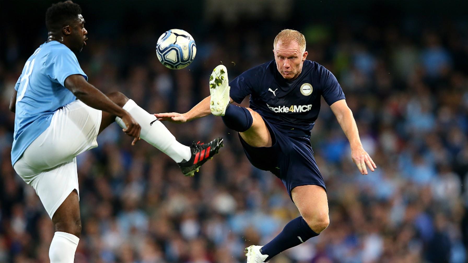 AERIAL BATTLE: Kolo Toure leaps alongside Paul Scholes to win possession