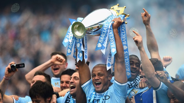 THAT WINNING FEELING: Vincent Kompany hoists the Premier League trophy aloft in 2014.