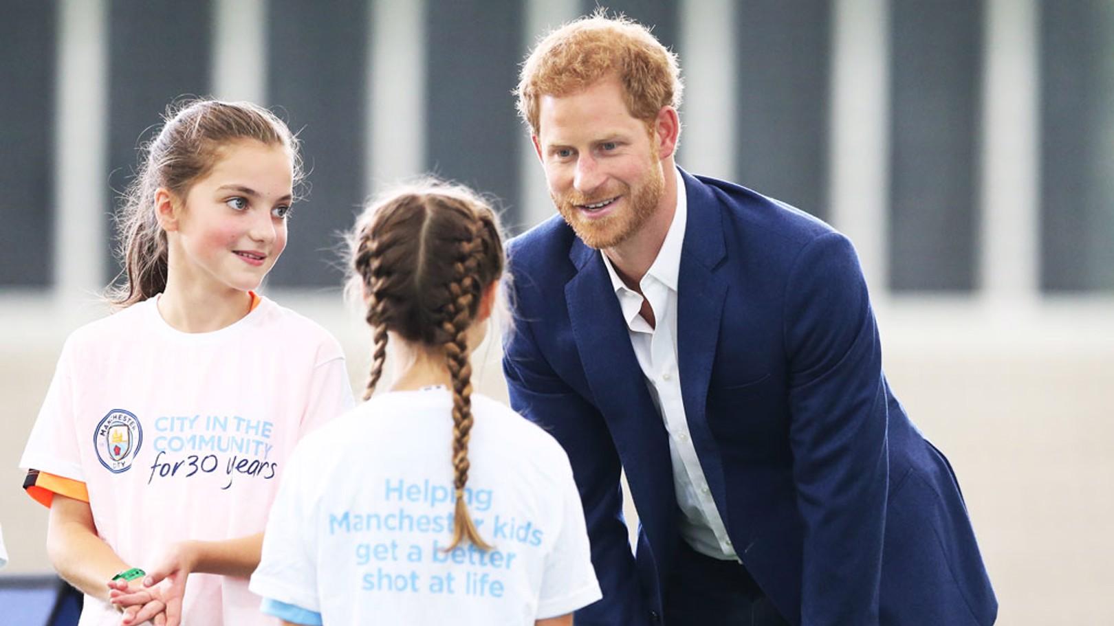 El Príncipe Harry charla con unas niñas que quieren ser futbolistas.