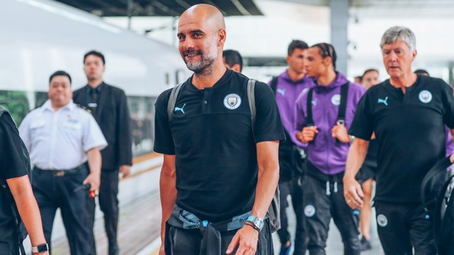 THE BOSS: Pep looks relaxed as he boards the train to Nanjing.