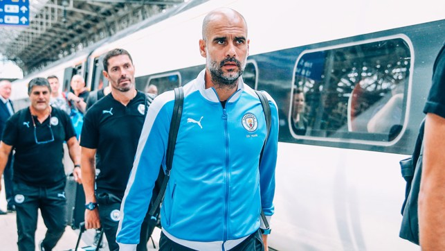 THE BOSS: Pep Guardiola prepares to board the train ahead of the journey to London
