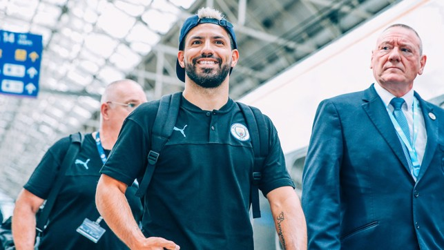 HAT'S THE WAY TO DO IT: Sergio Aguero is all smiles as he prepares to board the train to London