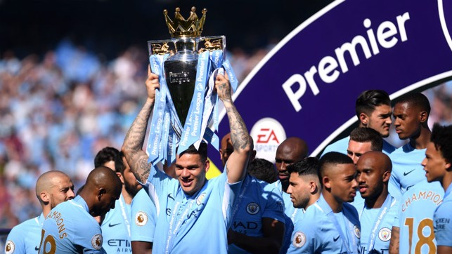 CHAMPIONS! Ederson lifts the Premier League trophy aloft