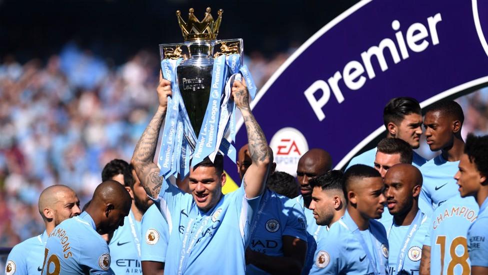 CHAMPIONS! Ederson lifts the Premier League trophy aloft