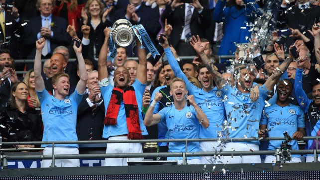 LIFTED: Kompany and the team celebrate their fourth piece of silverware this season