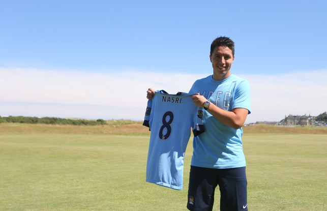 DOTTED LINE: Nasri holds up his new shirt after signing a contract extension in 2014
