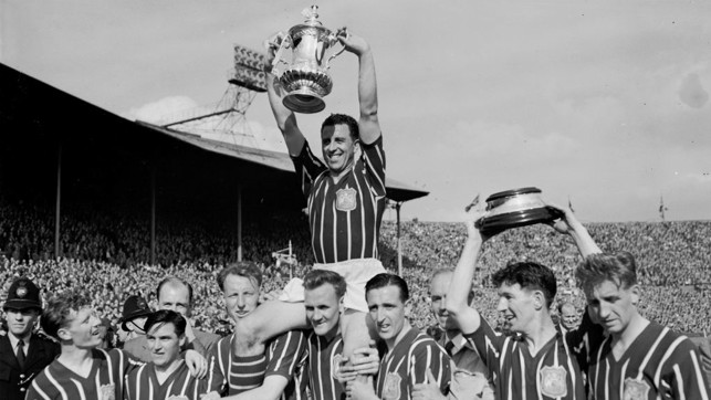 1956: Roy Paul lifts the FA Cup trophy with his City team mates.