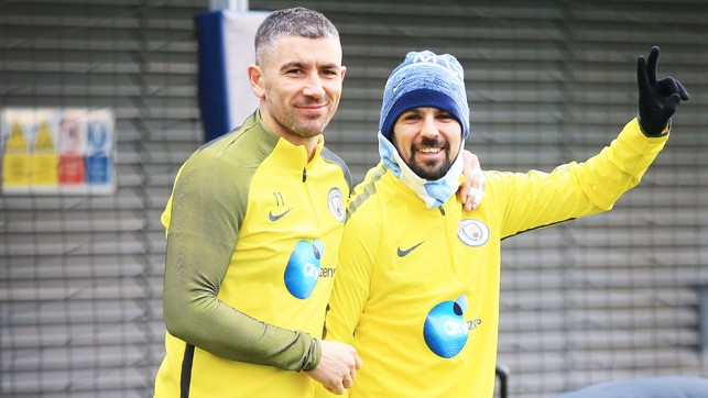 UP TO SOMETHING: Kolarov and Nolito have a cheeky grin on their faces as they come out for training...