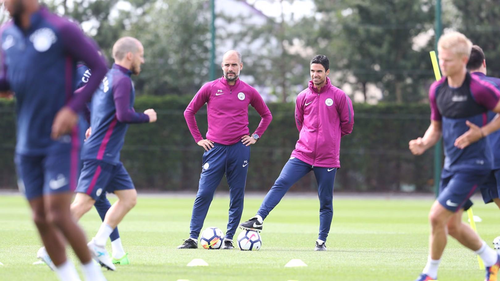 Pep Guardiola y Mikel Arteta observan la acción