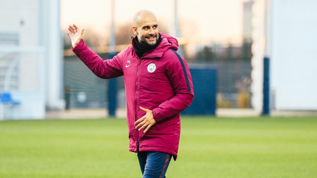 HI: Pep Guardiola waves at one of his players