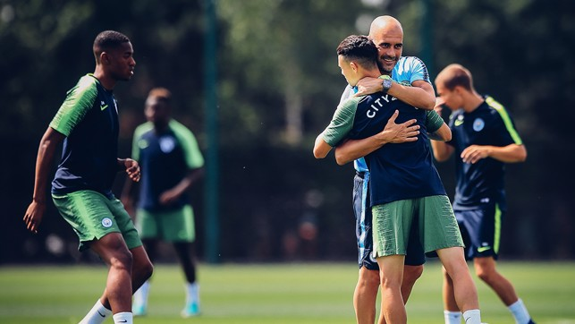 GLAD TO BE BACK: Pep gives Phil Foden a big hug to welcome him back to the CFA.