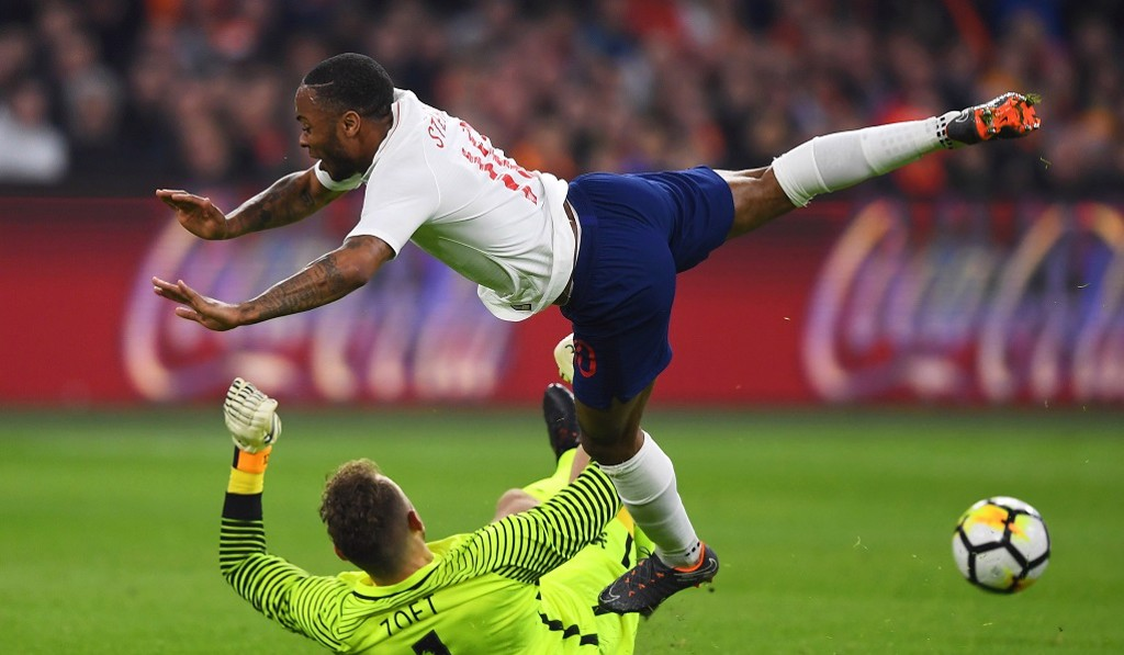 SOARING STERLING: Raheem leaps to avoid contact with Dutch keeper Joroen Zoet