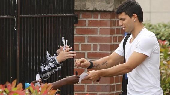 2011. Ha corrido la voz y Sergio Agüero saluda y firma autógrafos a los seguidores del congregados en el hospital de Manchester antes de las pruebas médicas
