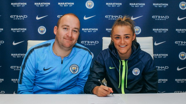 DELIGHTED: All smiles as Georgia puts pen to paper, alongside Nick Cushing