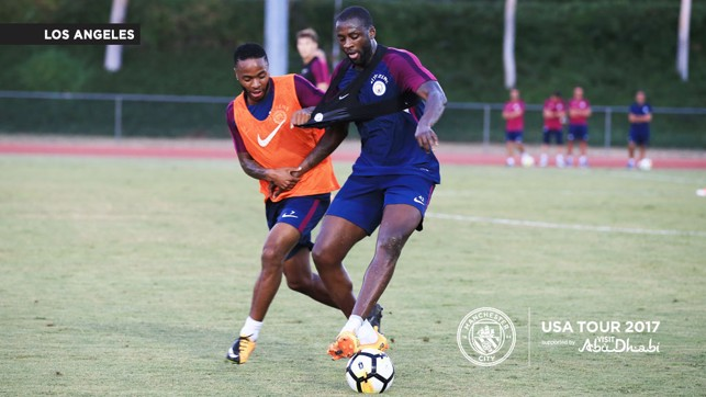 BATTLING FOR THE BALL: Yaya holds off a challenge from Raheem.