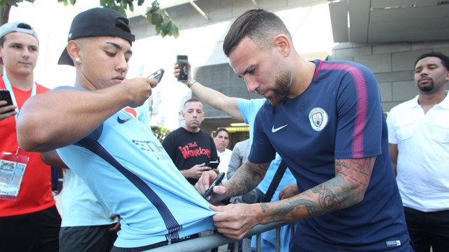 SIGNING SHIRTS: Otamendi takes time out to sign this fan's shirt.