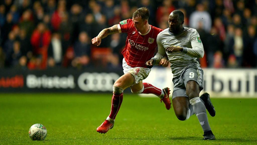 Aden Flint y Romelu Lukaku pugnan por el balón durante los cuartos de final de la Copa de la Liga entre Bristol City y Manchester United.