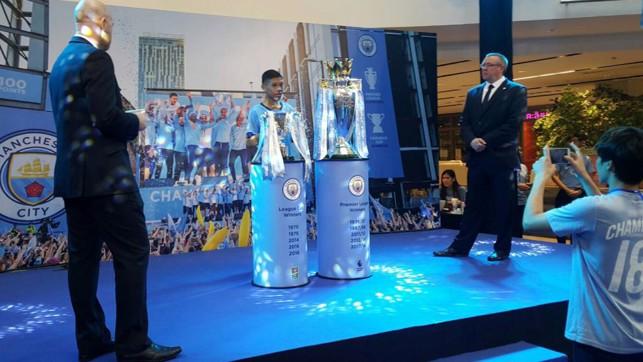 แฟนบอลต่อคิวยาวเหยียดเพื่อจะได้ถ่ายรูปร่วมกับสองถ้วยแชมป์ของแมนฯซิตี้ ถ้วยพรีเมียร์ ลีก และถ้วยคาราบาวคัพ