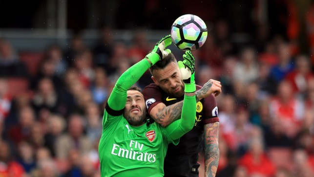 BATTLE: Otamendi attempts to deny Ospina from collecting the cross.
