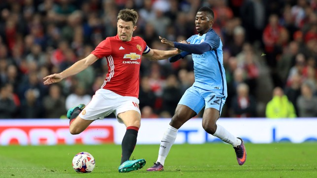 Carrick and Kelechi battle for the ball