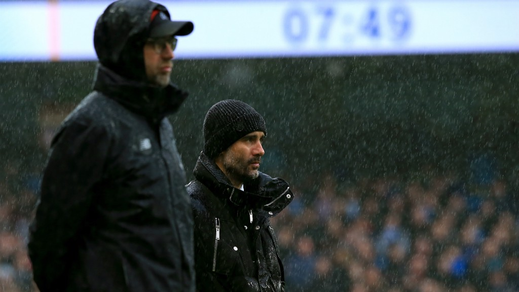 ONLOOKERS: Pep and Klopp battle the Manchester rain on the touchline