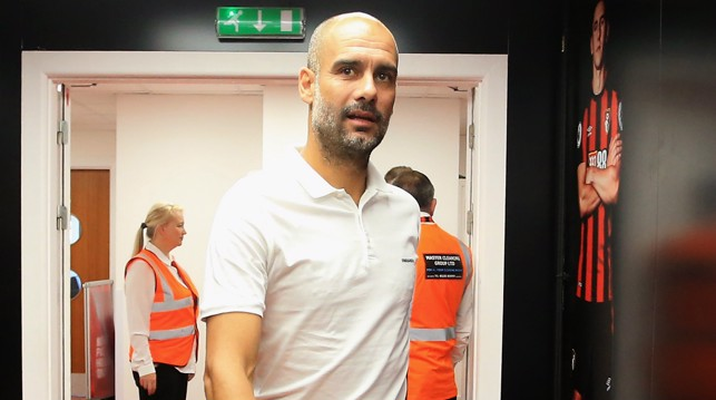 BOSS IS  IN THE BUILDING: Pep leads his players into the away dressing room