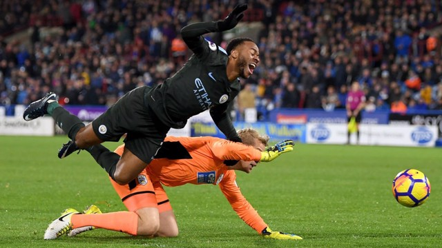 PENALTY: Raheem Sterling is brought down by 'keeper Jonas Lossl and referee Craig Pawson points to the spot.