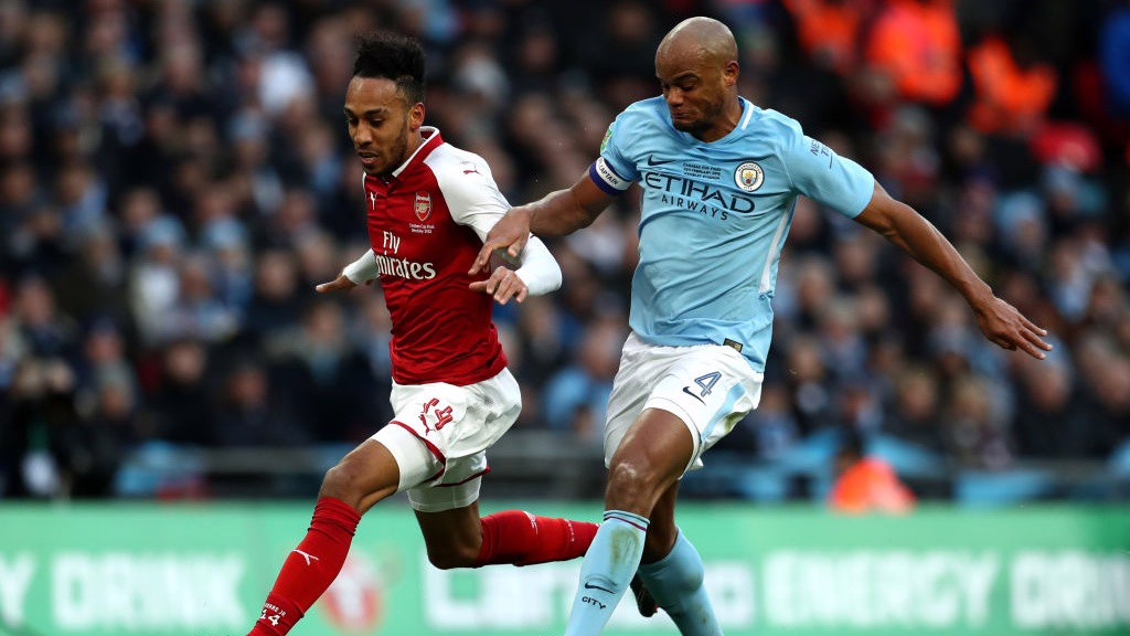 LEADER: Vincent Kompany makes a crucial tackle with Aubameyang through on goal