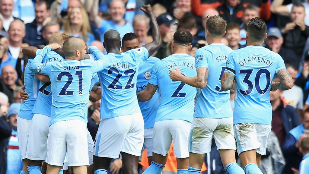 SEA OF BLUE: The team rush over to congratulate Sergio Aguero on the opener