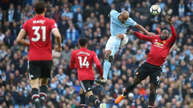 POWER: Vincent Kompany beats compatriot Romelu Lukaku in the air.