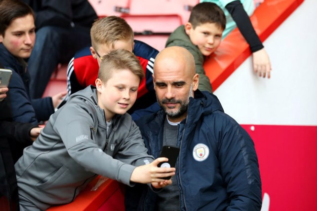 CENTRE OF ATTENTION: The boss poses for a picture with some happy young Bournemouth fans prior to kick-off