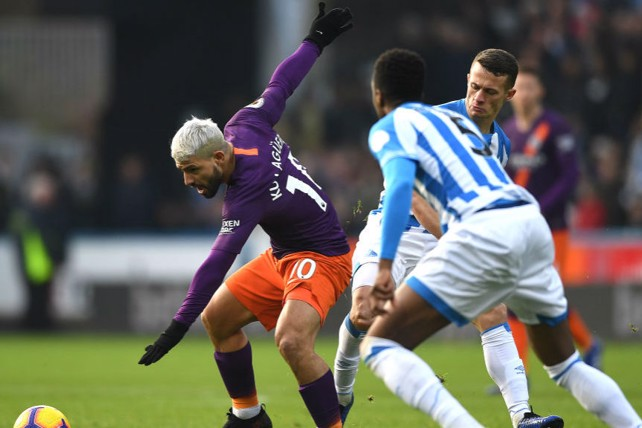AT ARMS LENGTH: Sergio Aguero looks to shield the ball from the Huddersfield defence