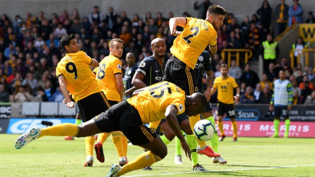 CONTROVERSIAL CALL: Willy Boly stoops to open the scoring for Wolves but replays showed the ball went in off his hand