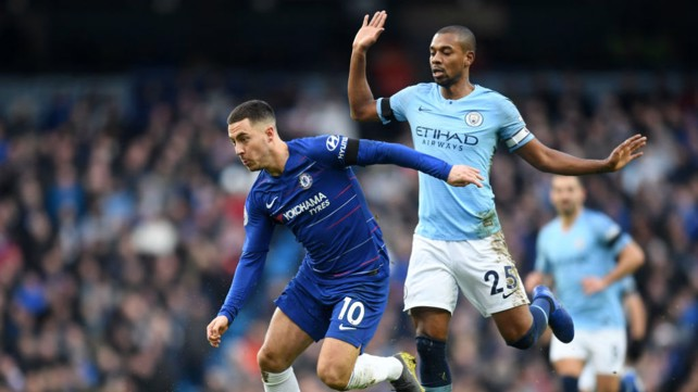 BATTLE: Fernandinho and Eden Hazard come head-to-head in the middle of the park.
