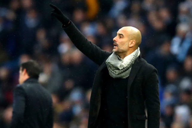 GLOVE STORY: Pep Guardiola is well wrapped up as he fires out instructions