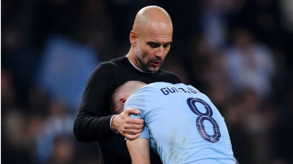 AGONY: Pep Guardiola consoles Ilkay Gundogan after the final whistle