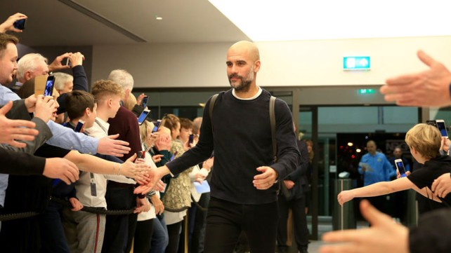 HI FIVE: Pep is greeted upon arrival at the Etihad Stadium