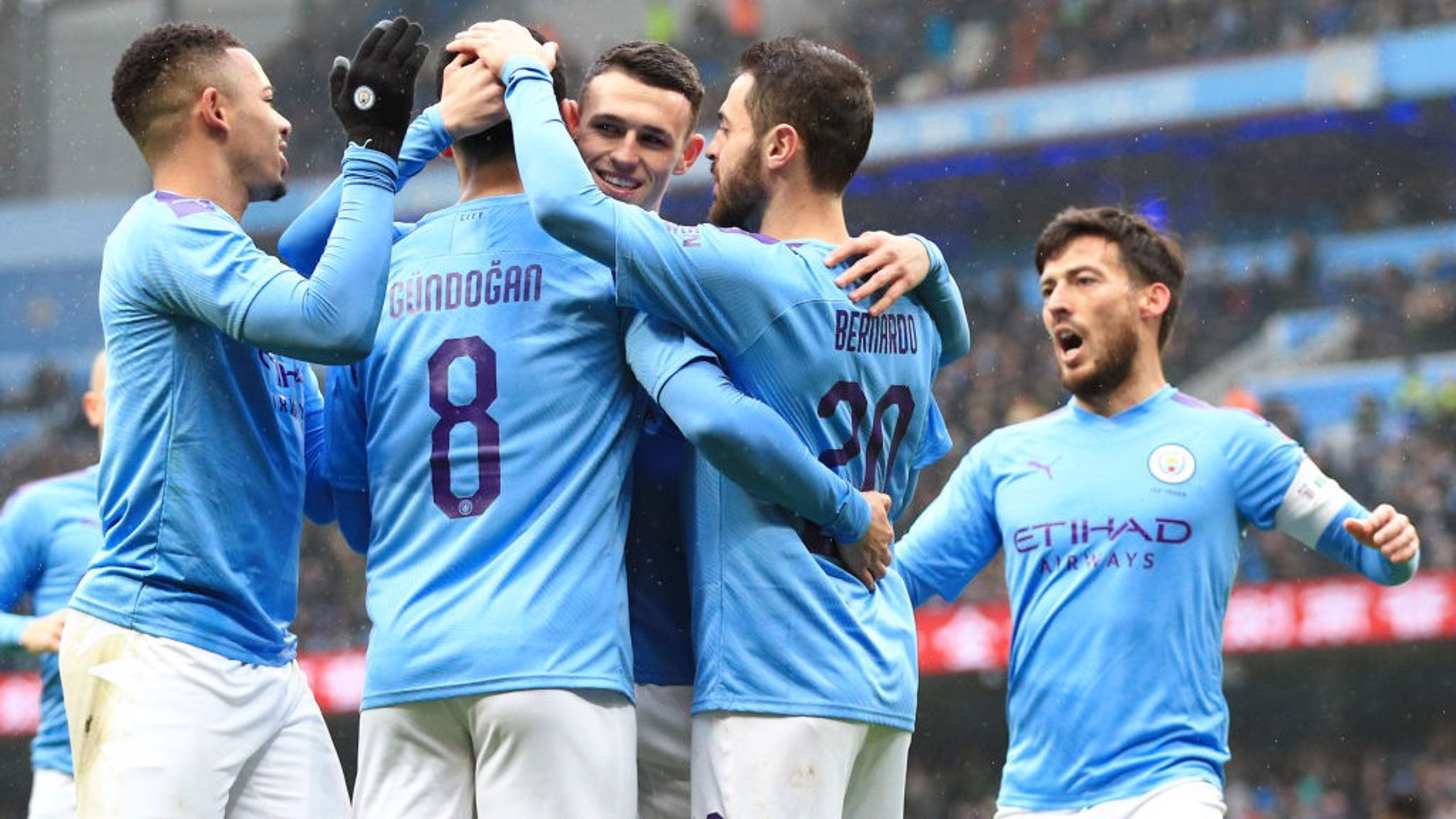 GROUP HUG: The players share the love after Gundogan's opening goal.