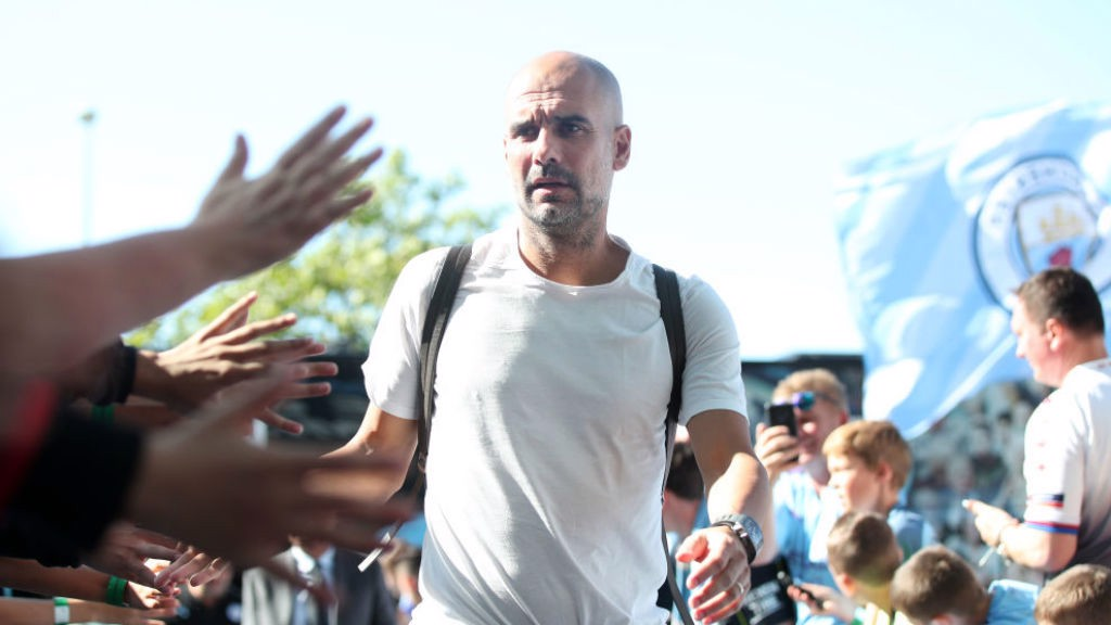 THE BOSS: Pep Guardiola greets the fans as he arrives at the Etihad