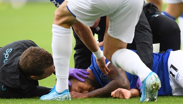 CONCERN: Theo Walcott lies on the ground after being stuck by Sterling's cross