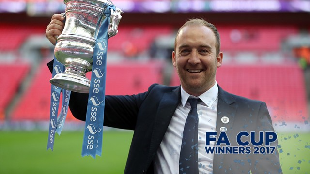 BIG SMILE: Manager, Nick Cushing poses with the trophy after his team is crowned champions.