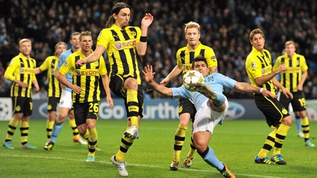 OUTNUMBERED: Aguero attempts to get a shot away during a Champions League tie between the sides in 2012.