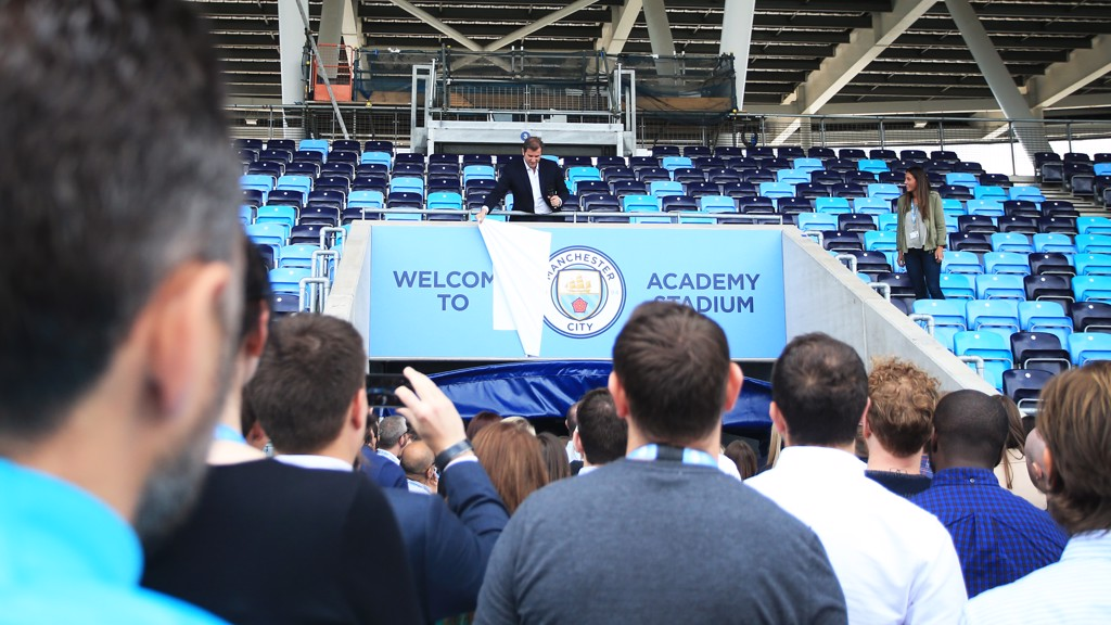 Manchester City's CEO Ferran Soriano unveils the crest in the Academy Stadium in front of staff