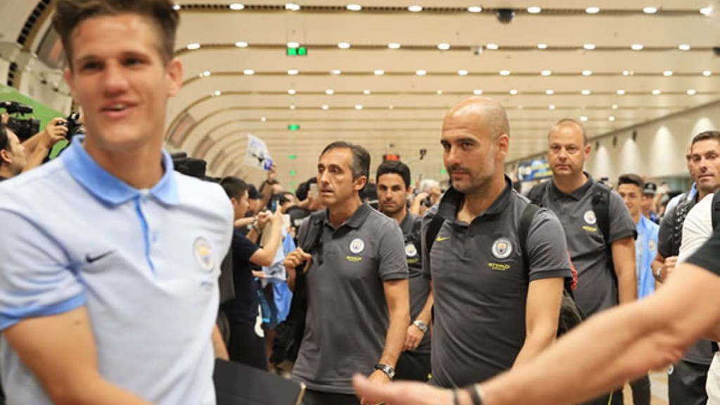 THE BOSS: Pep walks through arrivals in Beijing.