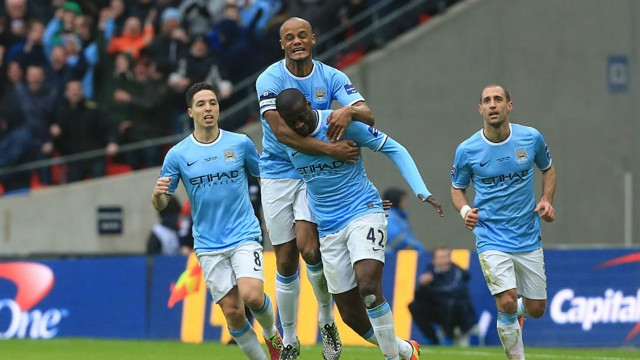 JOY: Yaya is mauled by his teammates after his screamer in the 2014 League Cup final.