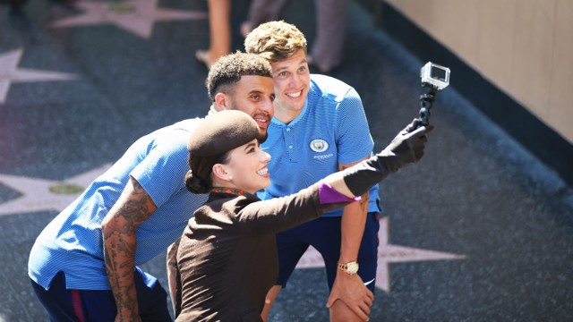 CHEESE: John Stones and Kyle Walker take a selfie with a member of the Etihad Airways cabin crew.