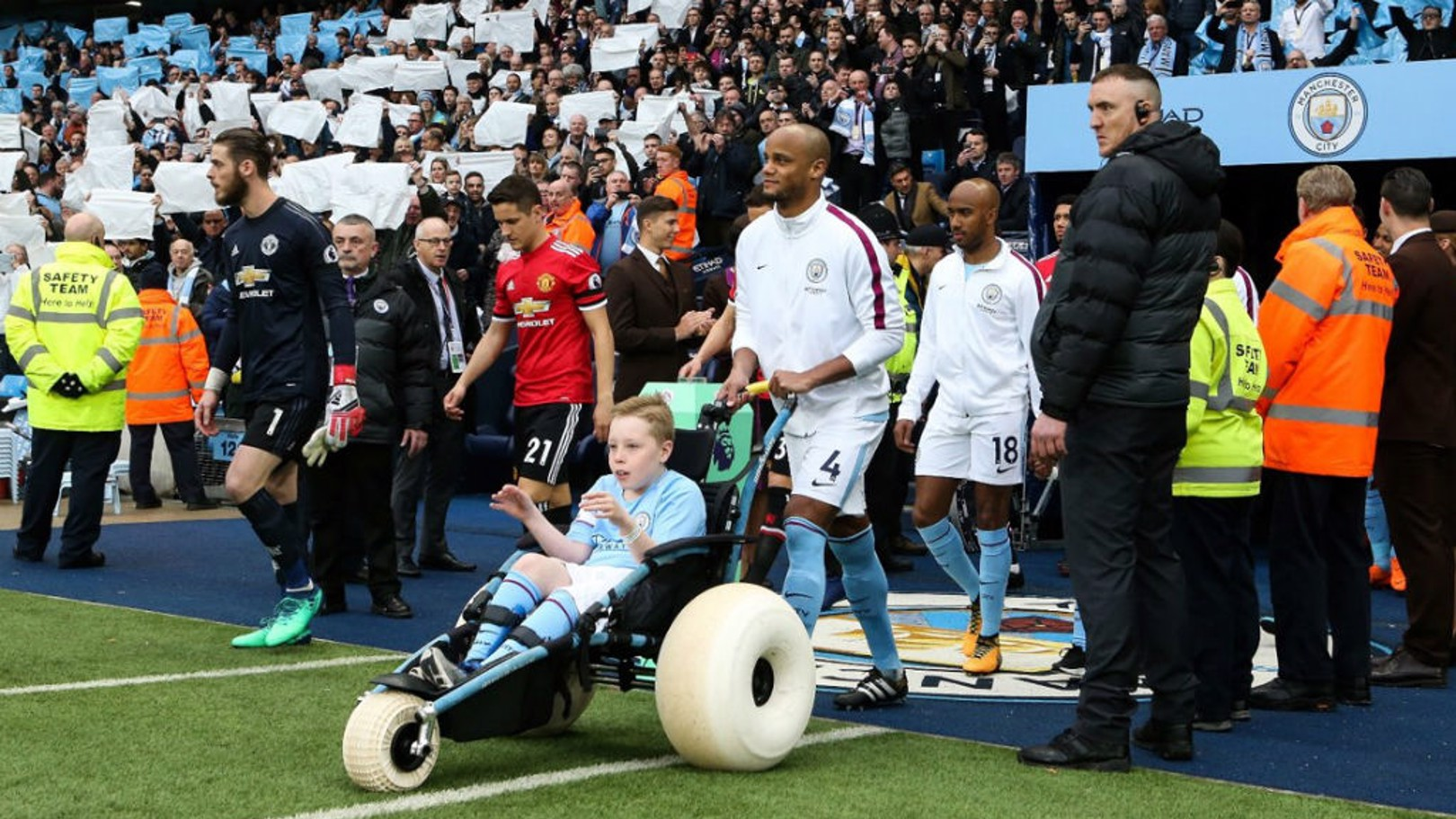 MAGIC MOMENT: Charlie Kay leads Manchester City out as mascot ahead of the Manchester derby