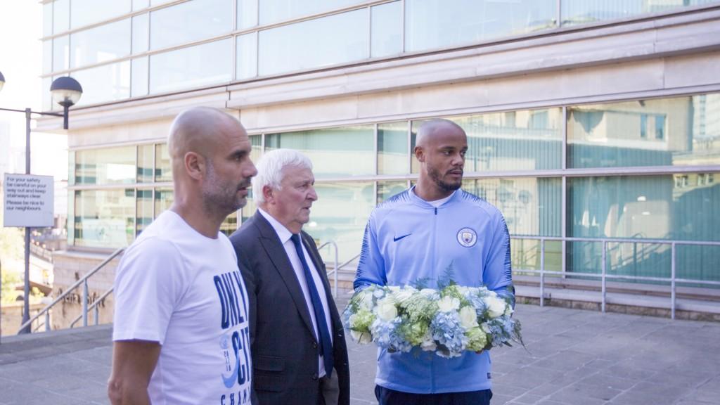 HOMENAJE. Guardiola, Kompany y Summerbee depositan un ramo de flores en el Manchester Arena.