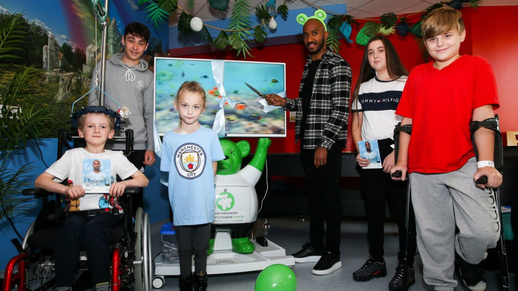 ALL TOGETHER NOW: Fabian Delph with some of the young Royal Manchester Children's Hospital patients during the unveiling of the 3D pain distraction unit